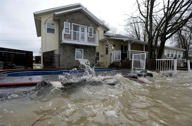 Rising water from the Ottawa River is nearly level with the deck and swimming pool at a home in Rockland, Ont., about 40 kilometres east of Ottawa, on Sunday, May 7, 2017.