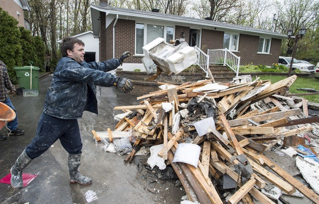 In this 2017 file photo, David Samuelson throws debris from his flooded house onto a pile on his driveway in the Pierrefonds borough of Montreal.
