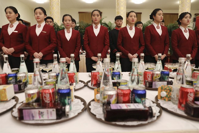 Chinese waitresses wait ahead a welcome banquet for the Belt and Road Forum at the Great Hall of the People in Beijing, Sunday, May 14, 2017.