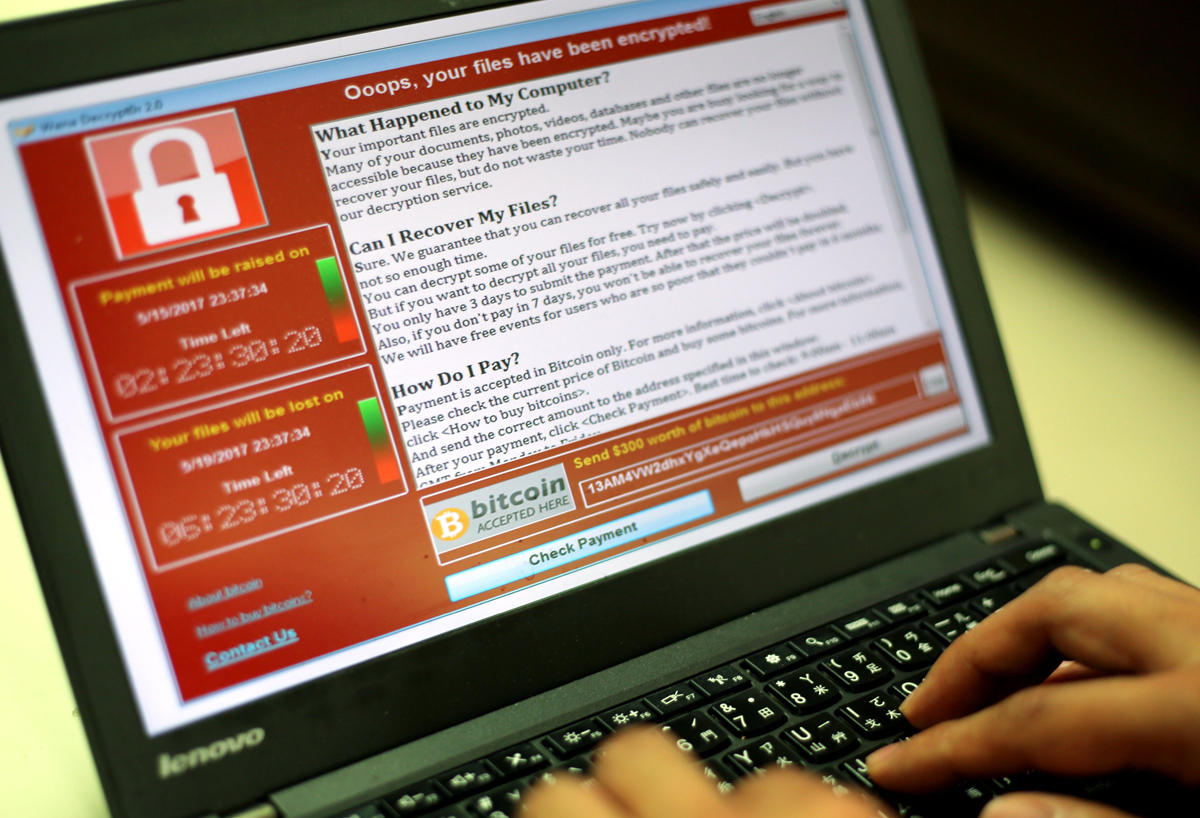 A programmer shows a sample of a ransomware cyberattack on a laptop.
