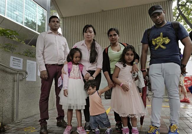 Ajith Pushpa Kumara, Vanessa Mae Rodel and her daughter Keana, Nadeeka Dilrukshi Nonis and her son Dinath and daughter Sethmundi Kellapatha, and Supun Thilina Kellapatha pose outside Hong Kong's immigration department in May 2017.