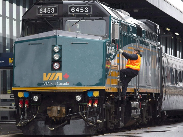 A Via Rail employee climbs aboard a locomotive at the train station in Ottawa on Monday, December 3, 2012.