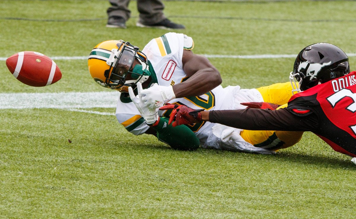 Edmonton Eskimos Bryant Mitchell (80) fumbles a catch in the endzone under pressure from Calgary Stampeders Osagie Odiase (32) during first half CFL pre-season action in Edmonton, Alta., on Sunday June 11, 2017. THE CANADIAN PRESS/Amber Bracken.