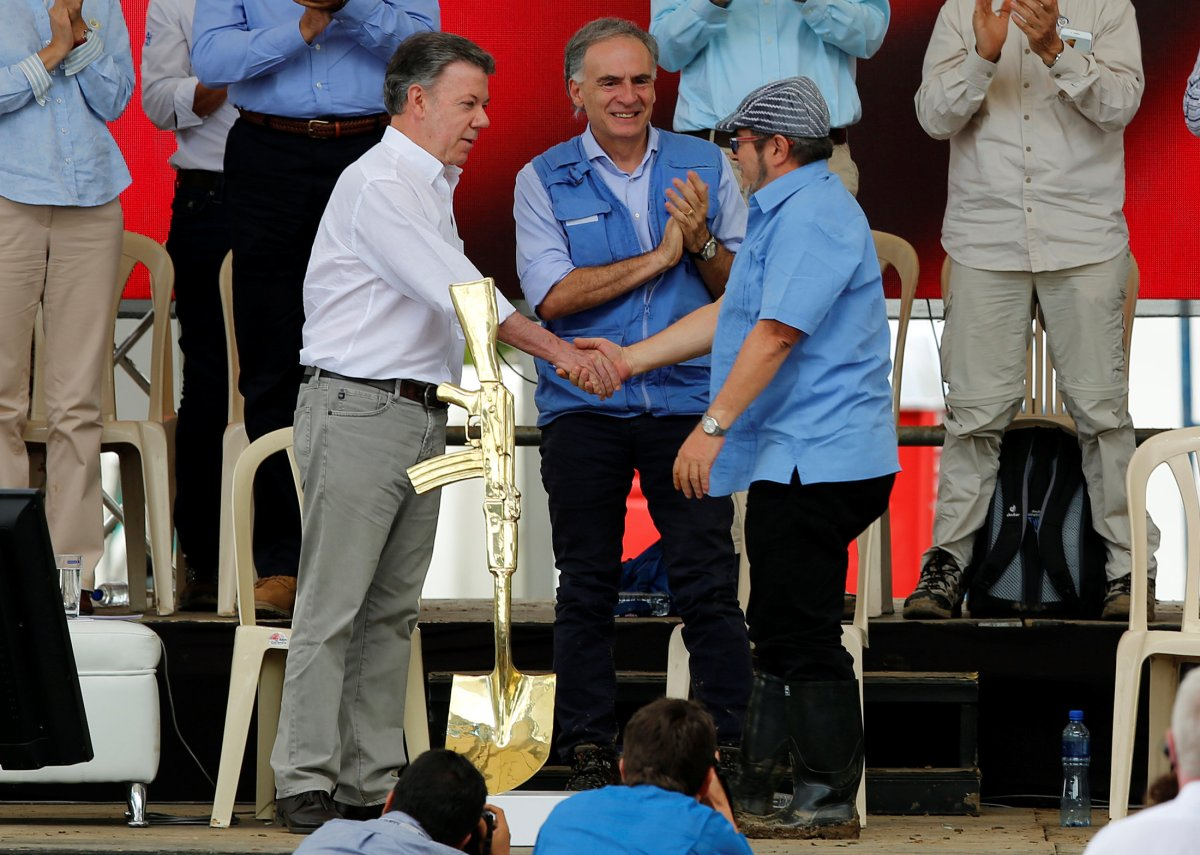 Colombia's Marxist FARC rebel leader Rodrigo Londono, also known as Timochenko, Colombian President Juan Manuel Santos and Jean Arnault, the UN Secretary-General's Special Representative for Colombia and Head of the UN Mission to Colombia, attend the final act of abandonment of arms in Mesetas, Colombia June 27, 2017.