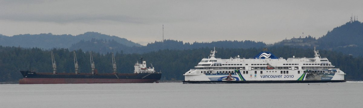 The BC Ferries' vessel Coastal Inspiration passes a freighter anchored off Vancouver Island as it heads for the terminal at Nanaimo, BC, Canada. The ferry was coming from Horseshoe Bay on the British Columbia mainland.