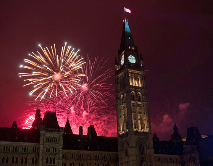 Fireworks light up the sky red behind the Peace Tower