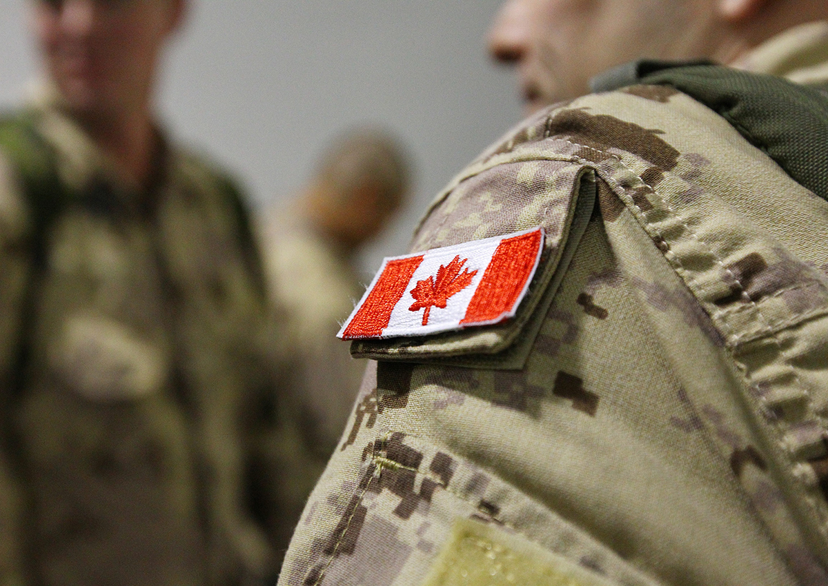 The Canadian flag is seen on the shoulder of a soldier waiting to board an Airbus CC-150 Polaris at CFB Trenton in Trenton, Ont., on Oct. 16, 2014.