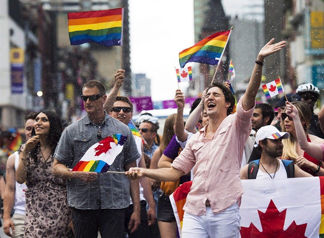 Prime Minister Justin Trudeau is splashed with water as he waves a flag at the annual Pride Parade in Toronto on Sunday, July 3, 2016.