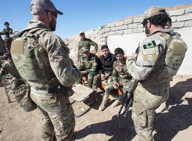 Canadian special forces soldiers, left and right, speak with Peshmerga fighters at an observation post, Monday, Feb. 20, 2017 in northern Iraq.