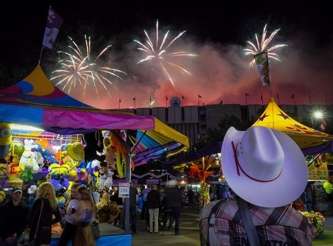 A visitor watches the fireworks display from the midway at the Calgary Stampede in Calgary, Saturday, July 9, 2016.