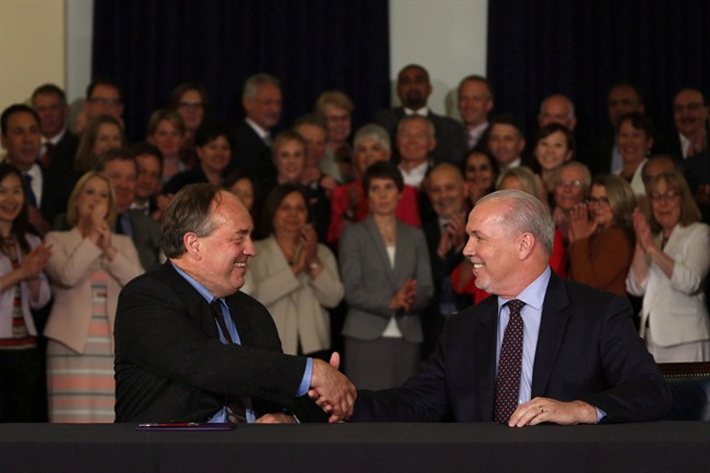 B.C. NDP leader John Horgan and B.C. Green party leader Andrew Weaver shake hands after signing an a governing agreement.