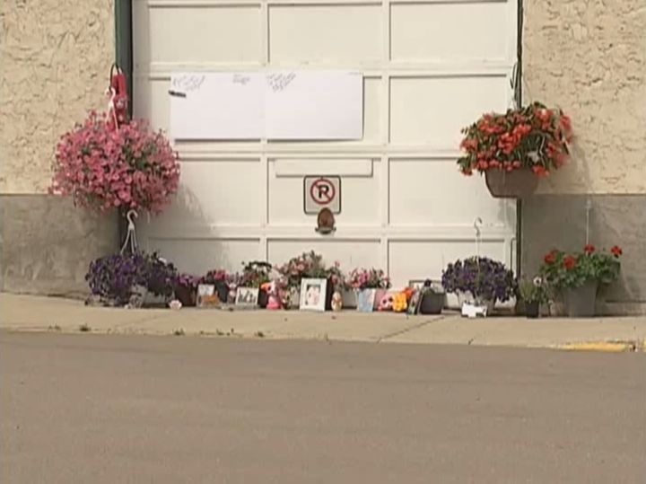 A memorial grows outside a maintenance yard in Dewberry, Alta. where a 21-year-old woman was killed by a falling lawn mower. June 15, 2017.