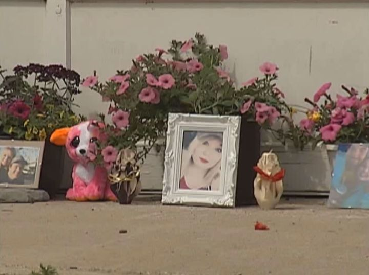 A memorial grows outside a maintenance yard in Dewberry, Alta. where a 21-year-old woman was killed by a falling lawn mower.