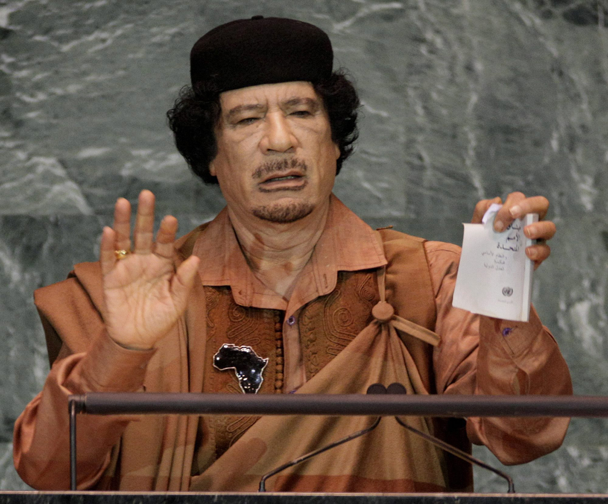 In this Sept. 23, 2009 photo, Libyan leader Moammar Gadhafi shows a torn copy of the UN Charter during his address to the 64th session of the United Nations General Assembly.