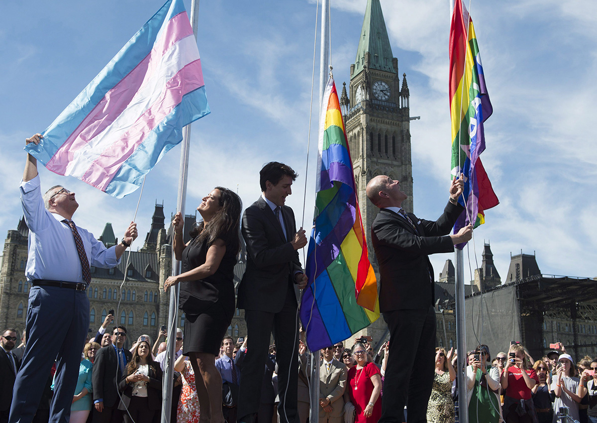 Public Safety and Emergency Preparedness Minister Ralph Goodale(left), Minister of Justice and Attorney General of Canada Jody Wilson-Raybould, Canadian Prime Minister Justin Trudeau and Liberal MP Randy Boissonnault raise the pride and transgender flags on Parliament Hill in Ottawa, Wednesday June 14, 2017.