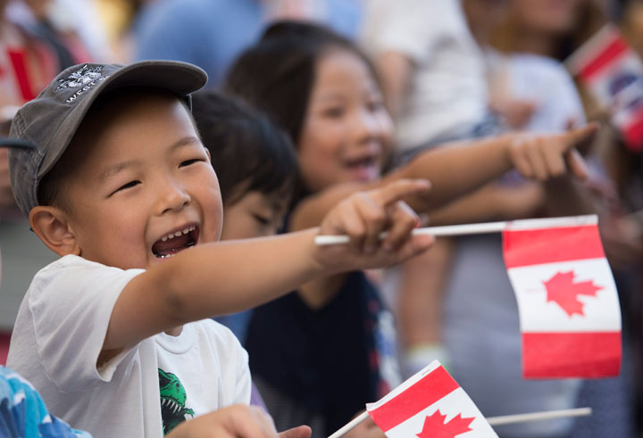 A young boy smiles as he watches the annual Canada Day parade