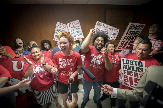Minneapolis city council candidate Ginger Jentzen, centre, celebrates with other supporters of the $15 minimum wage increase after it was passed by city council on June 30, 2017.