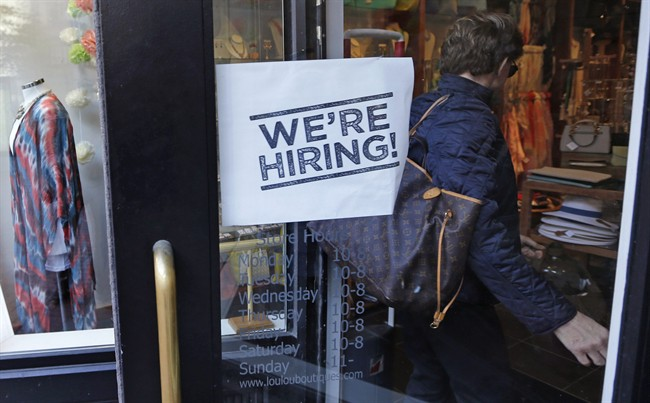"FILE - In this Wednesday, May 18, 2016, file photo, a woman passes a ""We're Hiring!"" sign while entering a clothing store in the Downtown Crossing of Boston."