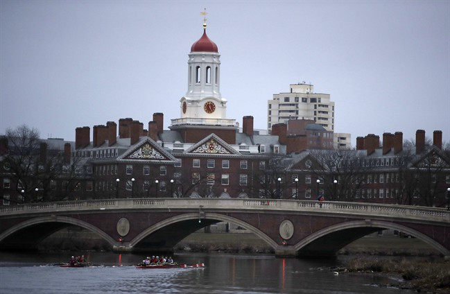 FILE - In this March 7, 2017 file photo, rowers paddle down the Charles River near the campus of Harvard University in Cambridge, Mass.