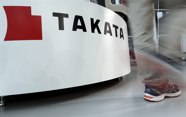 In this May 10, 2017 photo, a visitor walks past the logo of Takata Corp. at a Toyota showroom in Tokyo.