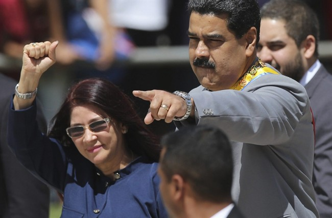 Venezuela's President Nicolas Maduro, right, and first lady Cilia Flores greet supporters upon arrival to a military parade at Fort Tiuna in Caracas, Venezuela.