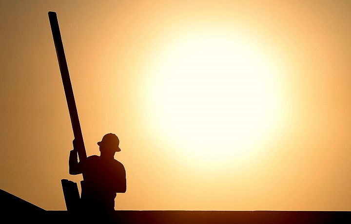 In this file photo, A construction worker is shown atop a roof at sunrise to beat daytime high temperatures.