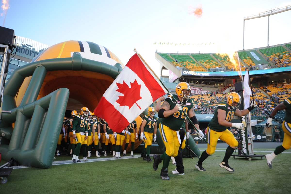 Edmonton Eskimos player #60 (OL) Justin Sorensen with player # 66 (OL) Matt O'Donnell run out onto the field before the first quarter of CFL game action between the Edmonton Eskimo's and the Montreal Alouettes at the Brick Field located at Commonwealth stadium in Edmonton Friday, June 30/2017.  (CFL PHOTO Walter Tychnowicz- ).