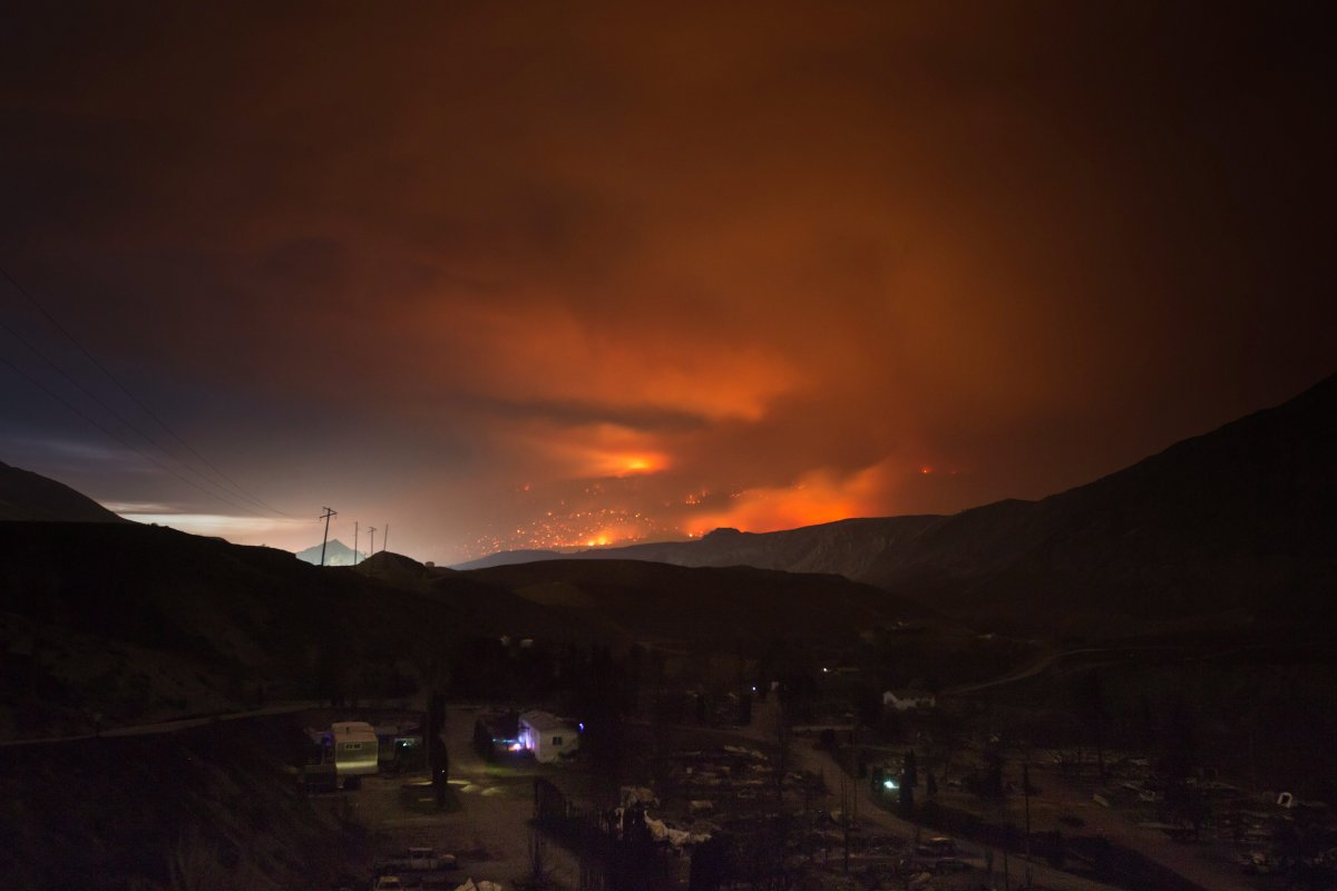 A wildfire burns on a mountain in the distance east of Cache Creek behind a trailer park that was almost completely destroyed by wildfire, in Boston Flats, B.C., in the early morning hours of Monday July 10, 2017.