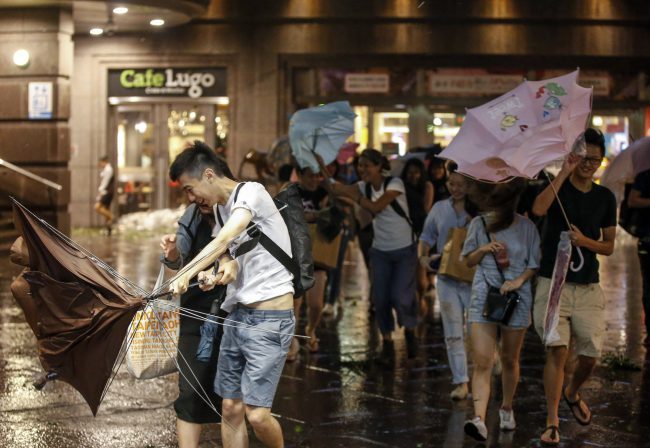 People shield themselves from strong wind and rain brought by Typhoon Nesat in Taipei, Taiwan, 29 July 2017.
