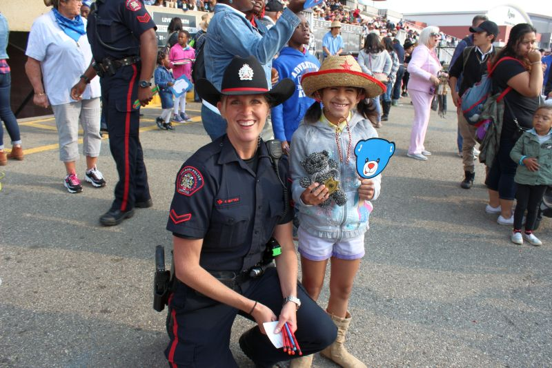 Ashlynn (right) and her teddy bear given to her by Officer Mattice (left) from the Calgary Police Service at the 2017 Calgary Stampede.