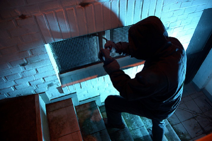 FILE PHOTO: A burglar breaking into a basement window.