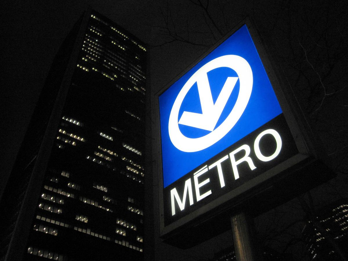 An outdoor metro sign in Montreal at night.