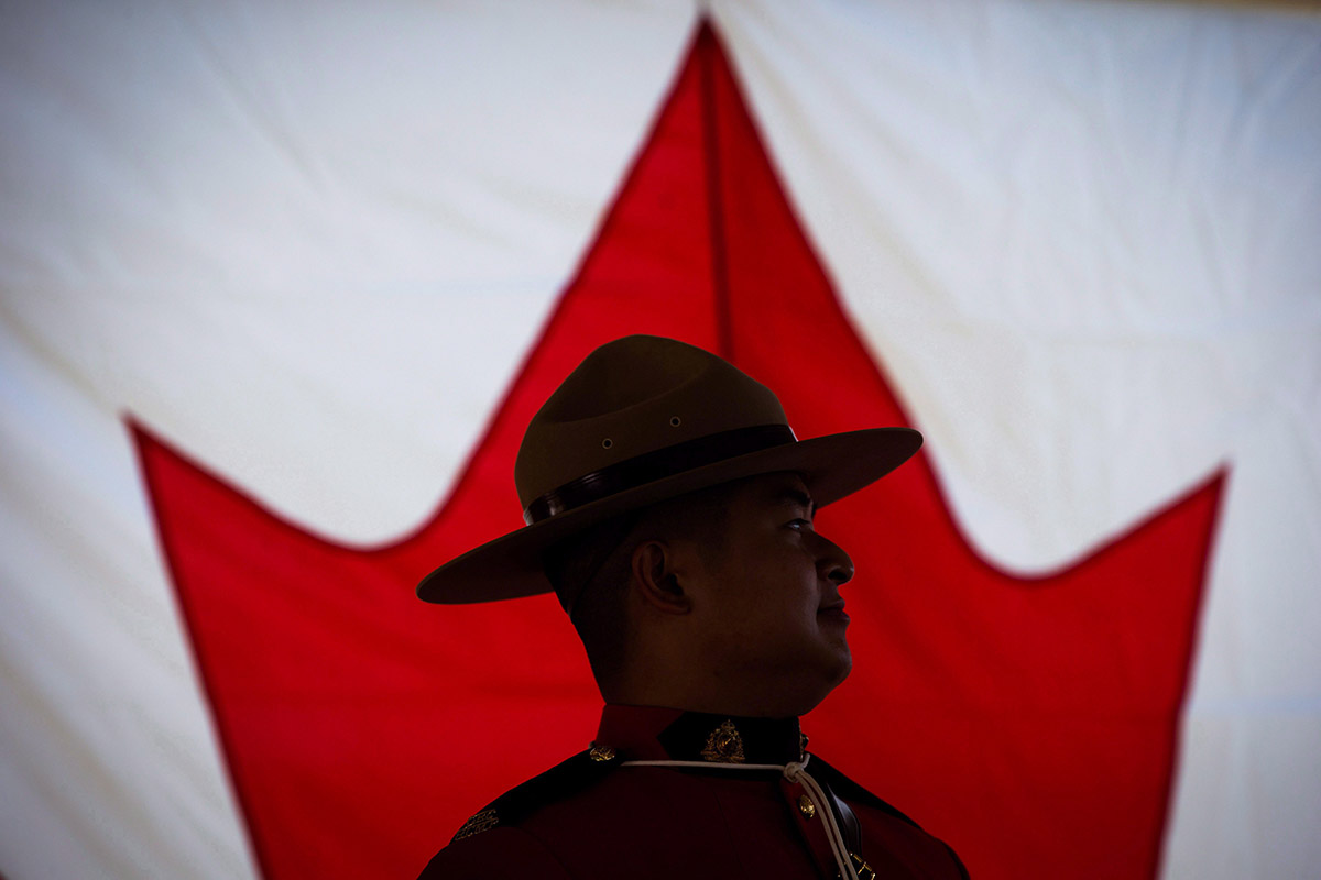 An RCMP officer is silhouetted against a Canadian flag during a special Canada Day citizenship ceremony in West Vancouver, B.C., on Saturday, July 1, 2017.