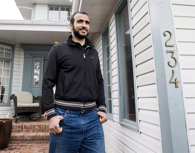 Omar Khadr walks out of his lawyer Dennis Edney's home to speak with the media in Edmonton, in spring 2015. The government is investigating who leaked information related to a settlement with Khadr to the press in early July.