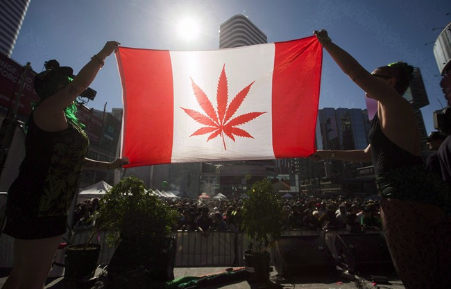 "Two people hold a modified design of the Canadian flag with a marijuana leaf in in place of the maple leaf during the ""420 Toronto"" rally in Toronto, April 20, 2016."