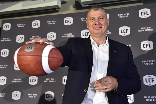 Randy Ambrosie holds a football as he speaks during a press conference in Toronto, Wednesday July 5, .