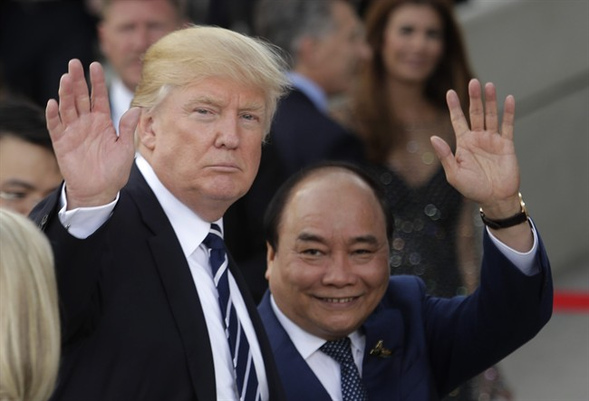 U.S. President Donald Trump, left, and Vietnamese Prime Minister Nguyen Xuan Phuc wave prior to a concert on the first day of the G-20 summit in Hamburg, northern Germany, Friday, July 7, 2017. The leaders of the group of 20 meet July 7 and 8.