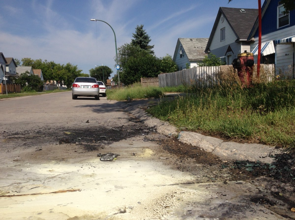Glass and debris are scattered on Gallagher Street where a vehicle caught fire Saturday.