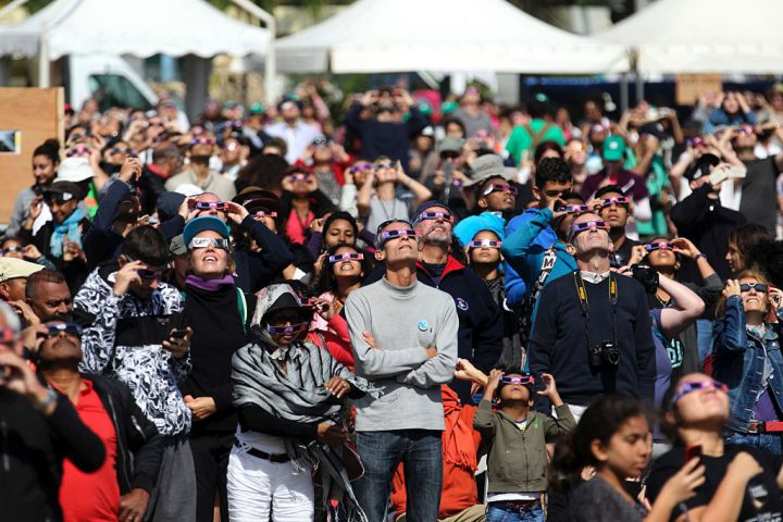 People look through eclipse viewing glasses, telescopes or photo cameras an annular solar eclipse, on September 1, 2016, in Saint-Louis, on the Indian Ocean island of La Reunion.