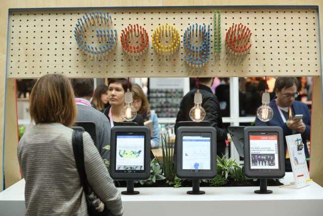 A visitor taps through news on a tablet at the Google Digital News Initiative stand at the Re:publica 17 conference on digital society in Berlin, Germany, May 8, 2017.
