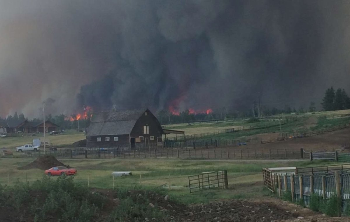 Wildfires burn behind a ranch near 100 Mile House.
