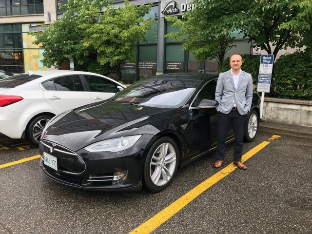 David Brown, 41, from Toronto, with his Tesla Model S, which he rents out through Turo.