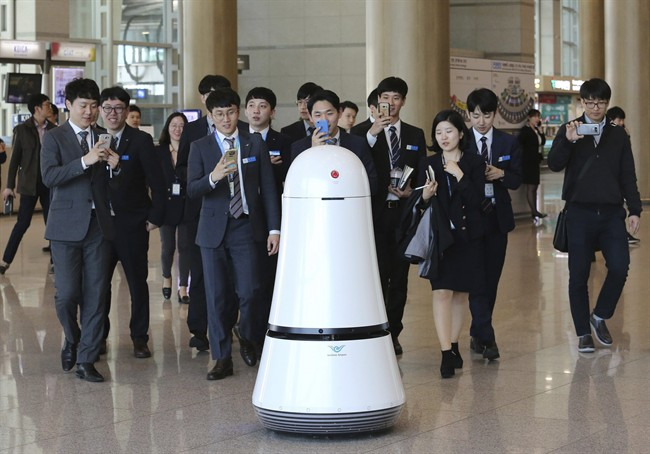 Employees of Incheon International Airport follow Troika, a self-driving robot made by LG Electronics, which moves around for visitors at the Incheon International Airport in Incheon, South Korea. Robots began roaming South Korea's largest airport last summer, helping travelers find their boarding gates and keeping its floors clean.