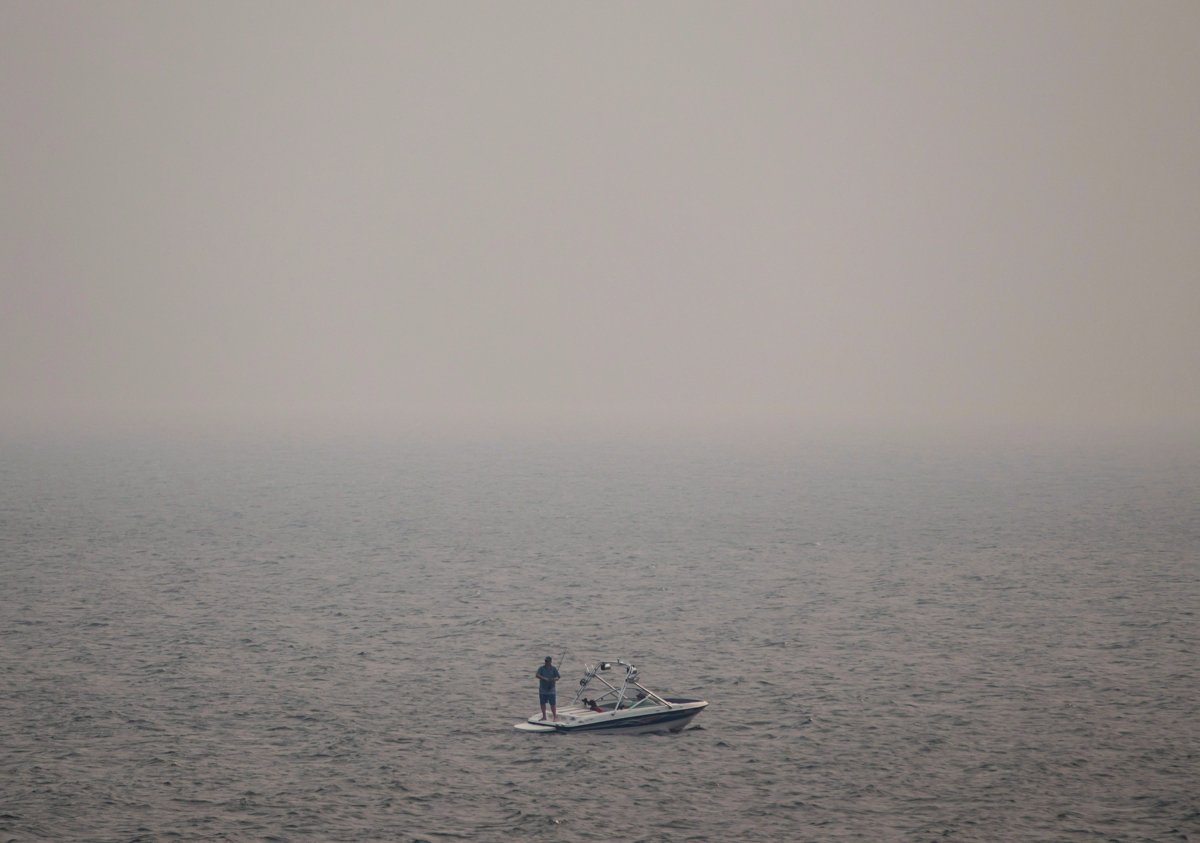 Thick smoke from wildfires fills the air as a man stands on a boat while fishing on Kamloops Lake west of Kamloops, B.C., on Tuesday August 1, 2017. Poor air quality persists throughout the southern half of British Columbia as tinder-dry conditions continue to fuel wildfires.