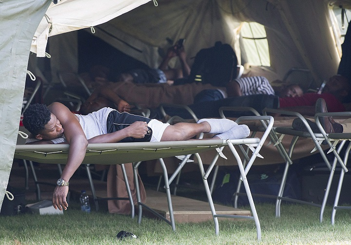 Asylum seekers rest in a tent at the Canada-United States border in Lacolle, Que., Thursday, August 10, 2017. THE CANADIAN PRESS/Graham Hughes