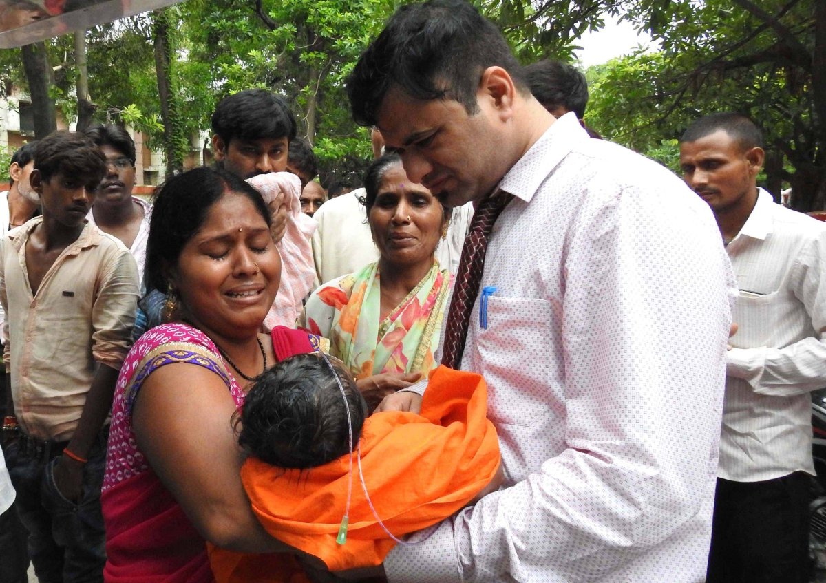 An Indian woman carries a child at the Baba Raghav Das Hospital in Gorakhpur, India, 11 August 2017 .
