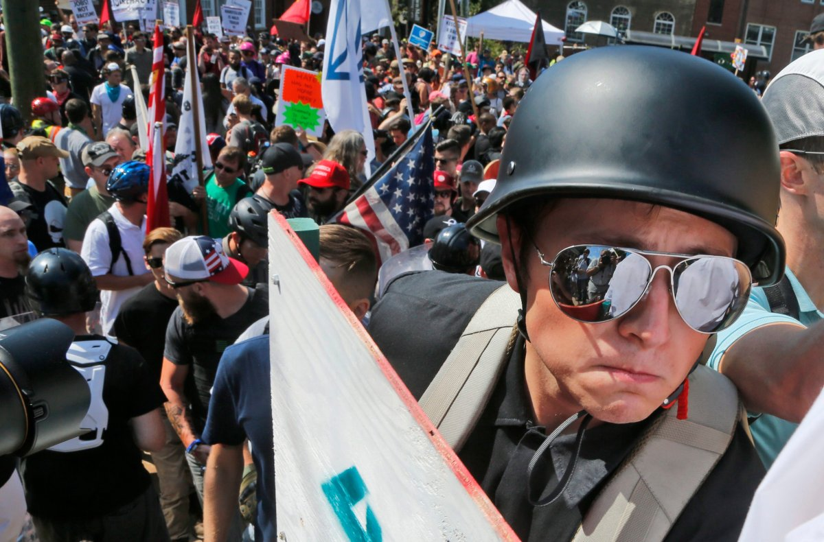 A white nationalist demonstrator with a helmet and shield walks into Lee Park in Charlottesville, Va., Saturday, Aug. 12, 2017.