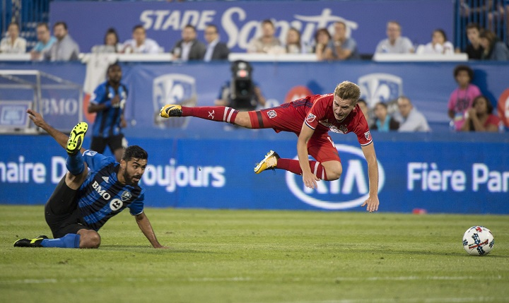 Chicago Fire midfielder Djordje Mihailovic trips over Montreal Impact defender Victor Cabrera during first half MLS action Wednesday, August 16, 2017 in Montreal. THE CANADIAN PRESS/Paul Chiasson