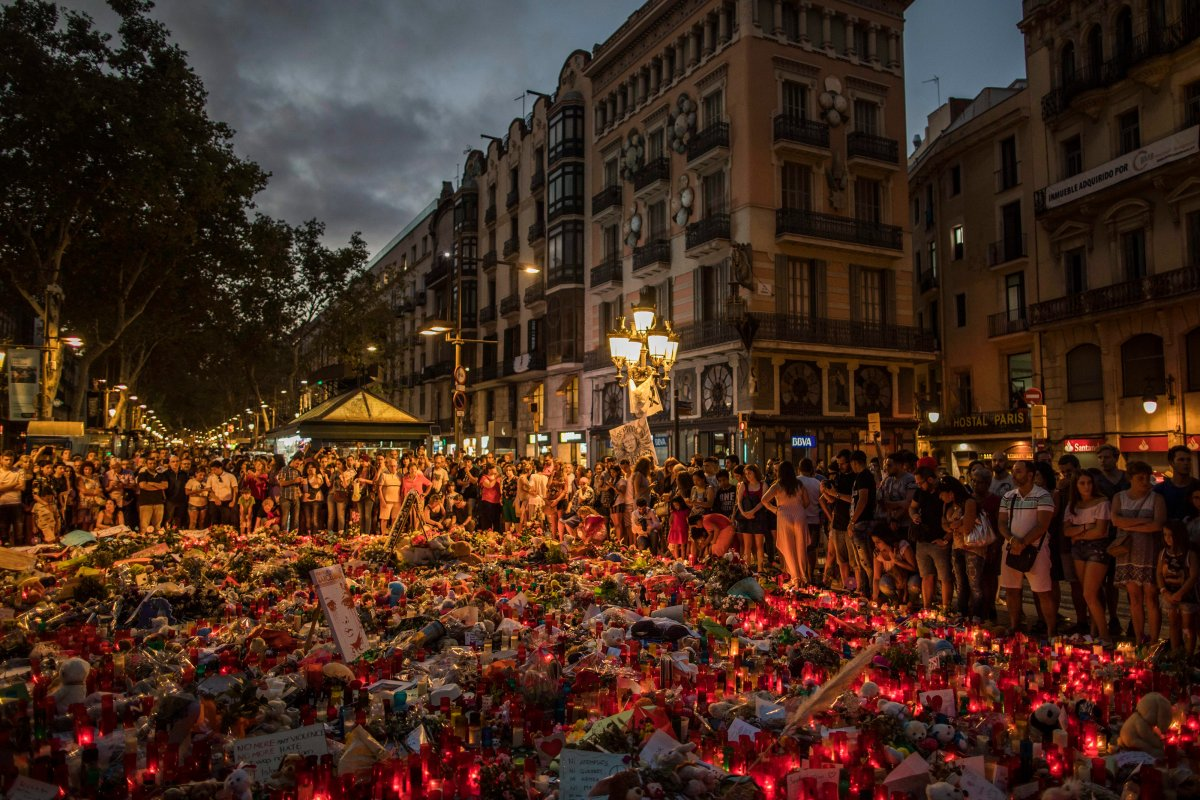 People stand next to candles and flowers placed on the ground, after a terror attack that left many killed and wounded in Barcelona, Spain, Monday, Aug. 21, 2017.