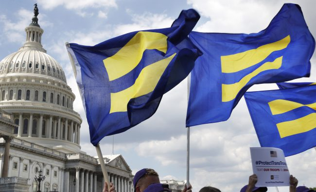 """FILE - In this July 26, 2017 file photo,   People with the Human Rights Campaign hold up """"equality flags"""" during an event on Capitol Hill in Washington, in support of transgender members of the military  ."""